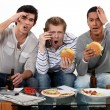 Three lads cringing at the television — Stock Photo