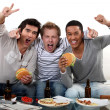 Three friends eating while watching television - Stock Photo