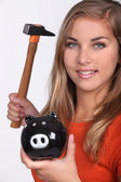 Young woman smashing her piggy bank — Stock Photo