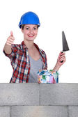 Portrait of high-spirited female bricklayer thumb up — Stock Photo