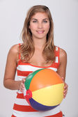 Young blond woman holding beach ball — Stock Photo