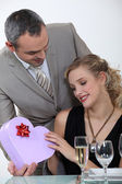 Blond receiving gift from boyfriend at romantic dinner — Stock Photo