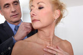 Man attaching necklace to wife — Stock Photo