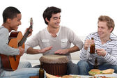 Three house-mates eating burgers and playing music — Stock Photo