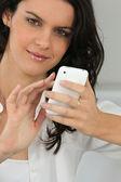 Hermosa joven escribiendo mensajes en su teléfono celular — Foto de Stock