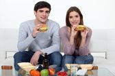 Mladý pár jíst hamburgery — Stock fotografie