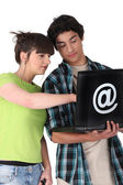 Teens with black computer — Stockfoto