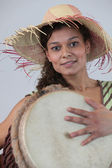 Woman wearing a straw hat and playing the djembe — Stock Photo