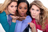 Three attractive women blowing kisses — Stock Photo
