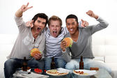 Three friends eating while watching television — Stock Photo