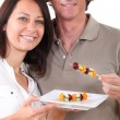 Couple preparing fruit kebabs - Stock Photo
