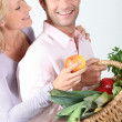 Stock Photo: Wife takes apple from basket.