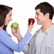 Couple exchanging apples — Stock Photo