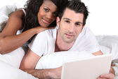 Mixed-race couple using laptop at home — Stock Photo