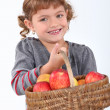 Young girl with a basket of apples — Stock Photo
