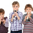 Three little girls playing flute — Stock Photo