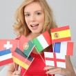 Fair haired woman with a variety of European flags — Stock Photo