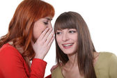 Young woman whispering a secret into her friend — Stock Photo