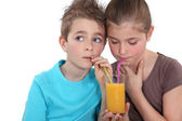 Children drinking a glass of orange juice — Stock Photo