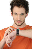 Casual young man checking his wrist watch — Stok fotoğraf