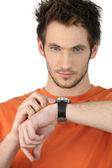 Dorywczo młody człowiek, sprawdzania jego zegarek na rękę — Zdjęcie stockowe