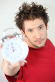 Young man holding an alarm clock — Stock Photo