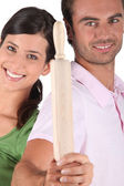 Couple holding rolling pin — Stock Photo