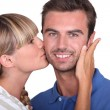 Young woman kissing a man - Stock Photo