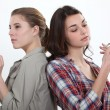 Girl lighting a cigarette as another snaps one in half - Stock Photo
