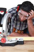 Man figuring out how to use saw — Stock Photo
