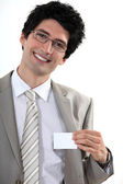 Businessman with glasses showing off business-card — Stock Photo