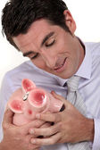 A businessman hugging his piggy bank. — Stock Photo