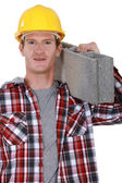 Studio portrait of bricklayer carrying concrete block — Stock Photo