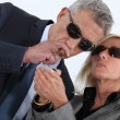 Mature gentlemsmoking cigar with blonde spouse showing off — Stock Photo #16154573