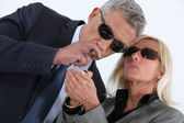 Mature gentleman smoking cigar with blonde spouse showing off — Stock Photo