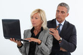 Mature business couple with a laptop — Stock Photo