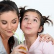 Stock Photo: Mother and daughter sharing a drink