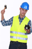 Construction worker breaking open a piggy bank — Stock Photo