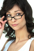 Attractive woman peering over her glasses — Stock Photo