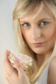 Blonde woman holding a pale pink rose — Stock Photo