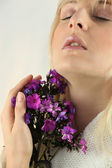 Woman smelling a bunch of flowers — Stock Photo