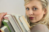 Woman carrying a stack of books — Stock Photo