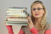 Attractive blond carrying pile of books — Stock Photo