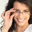 Brunette touching glasses fame — Stock Photo