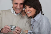 Married couple looking at photographs taken on digital camera — Stock Photo