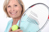 Elderly woman playing tennis — Stock fotografie