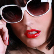 Close up of brunette wearing sunglasses - Stock Photo