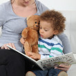 Woman reading a book to little boy on a couch - Stock Photo
