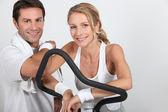 Пара носить спортивной одежды, явившись велотренажер — Стоковое фото