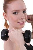 Girl lifting dumbbells, studio shot — Stock Photo